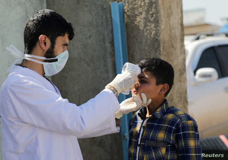 A health worker tests a Syrian boy as part of measures to control the coronavirus, in Azaz, Syria, March 11, 2020.