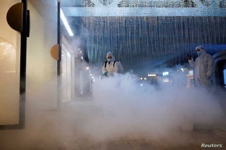 Volunteers in protective suits disinfect a shopping complex in Wuhan, Hubei province, the epicentre of China's coronavirus disease (COVID-19) outbreak, March 31, 2020.