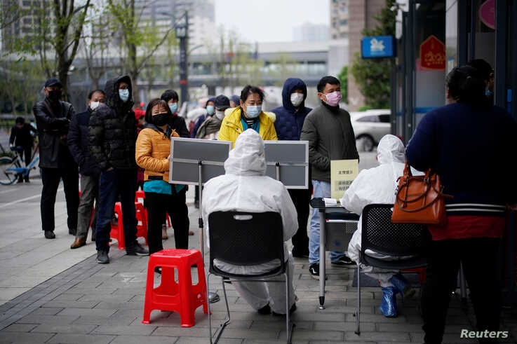 People wearing face masks line up outside a Hankou Bank branch in Wuhan, Hubei province, China, March 31, 2020.