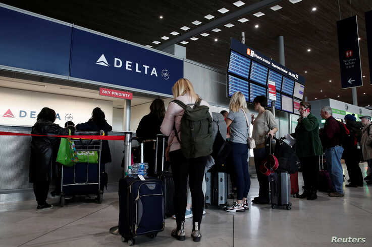 People line up at the Delta Air Lines ticketing desk inside Terminal 2E at Paris Charles de Gaulle airport in Roissy, after the U.S. banned travel from Europe, as France grapples with an outbreak of coronavirus disease, March 12, 2020.