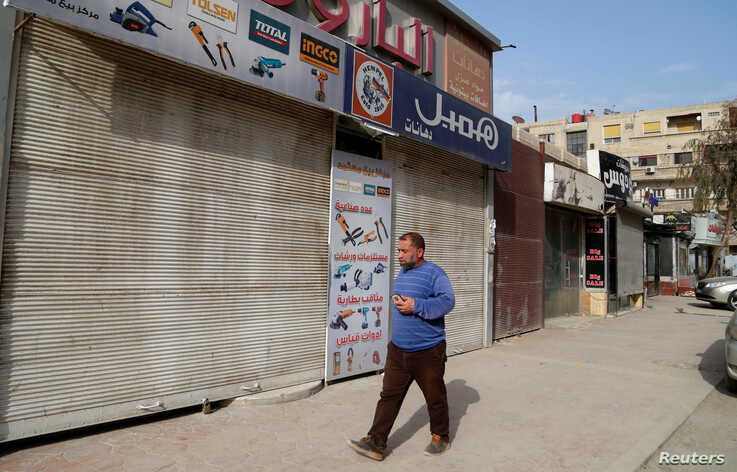 A man walks near empty shops as Syria confirmed its first case of the coronavirus disease (COVID-19), in Damascus, March 23, 2020.