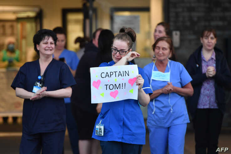 An NHS staff member wipes her eyes as she holds a sign to thank British veteran Captain Tom Moore who raised over 13 million…