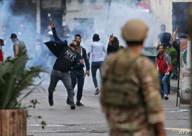 Lebanese protesters hurl rocks at soldiers in the northern port city of Tripoli on April 28, 2020, as anger over a spiralling…