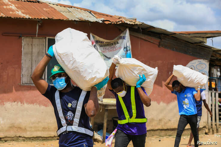 Volunteers carry sacks filled with food to distribute to vulnerable residents, during a lockdown by the authories in efforts to…