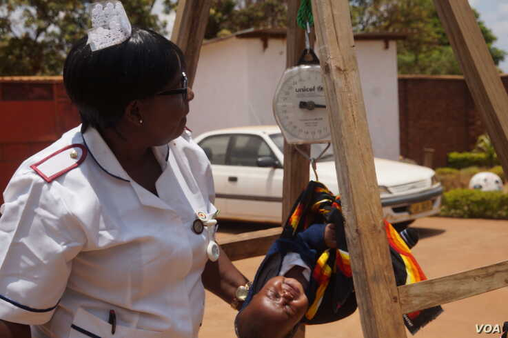 A nurse weighs a child at a health clinic in Malawi's capital, Lilongwe. Heath experts fear a coronavirus lockdown would intensify hunger among the country's poor. (Lameck Masina/VOA)