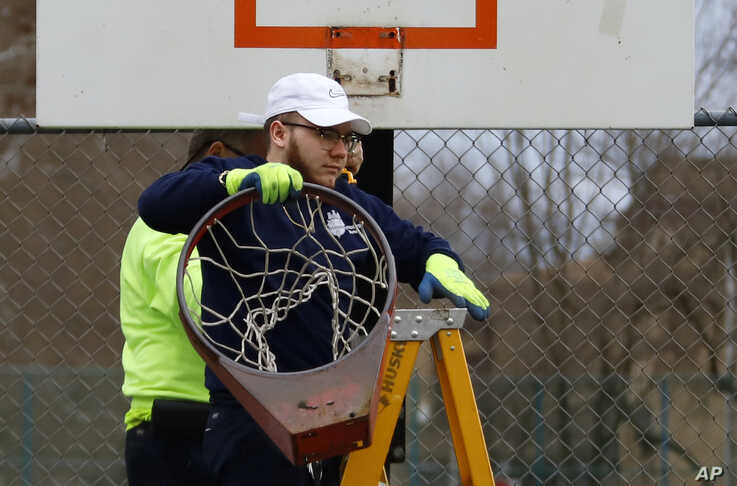 A Pittsburgh Public Works employee removes a basketball rim from a city court in an effort to encourage social distancing, March 30, 2020.