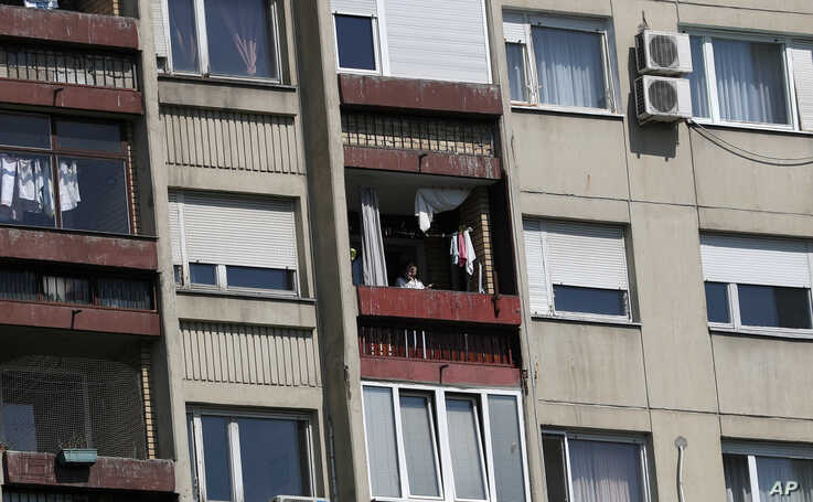 A woman stands on a a balcony during a curfew set up to help prevent the spread of coronavirus in Belgrade, Serbia, Sunday,…