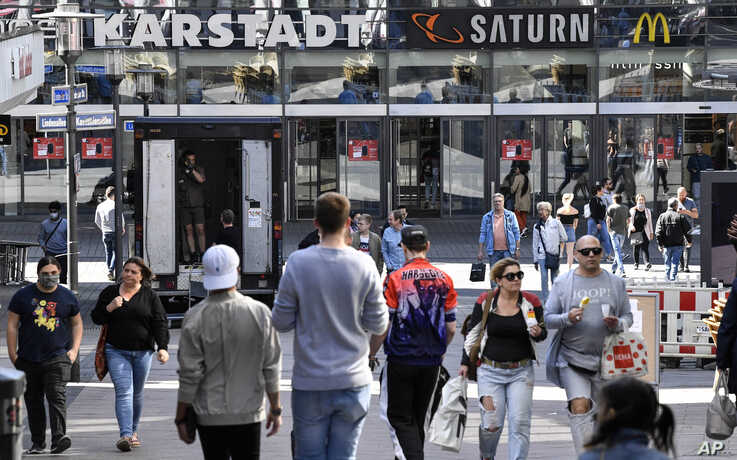 People walk to a shopping center as many smaller stores are allowed to open in Essen, Germany, Monday, April 20, 2020. Europe's…