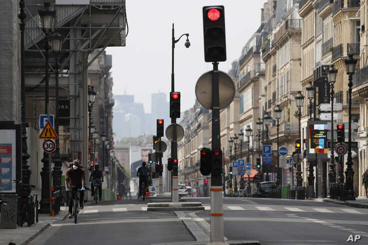 A man rides his bike in an empty street during a nationwide confinement to counter the COVID-19 in Paris, Tuesday, April 21,…