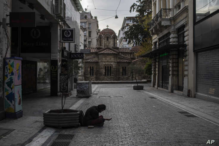 A beggar sits in an empty Ermou street in front of Kapnikarea church during lockdown measures by the Greek government to prevent the spread of coronavirus in Athens, on Tuesday, April 21, 2020.