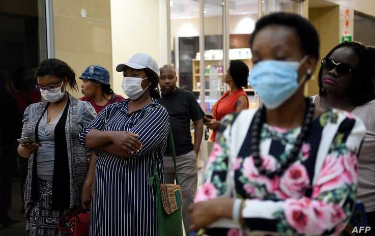 Customers wearing masks, queue at a supermarket in Gaborone, Botswana, March 31, 2020.