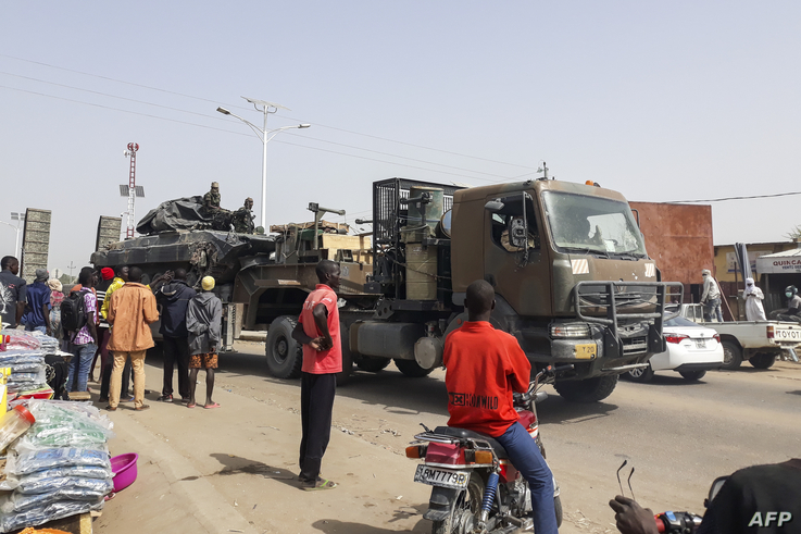 FILE - Bystanders look on as a tank is transported on a truck through the streets of N'Djamena, Chad, Jan. 3, 2020, as Chadian troops return from a mission fighting Boko Haram in neighboring Nigeria.