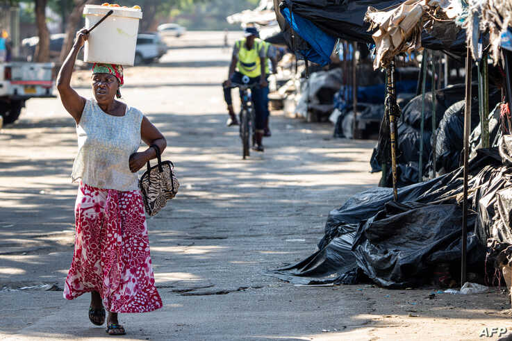 A vendor carries fresh produce as police officers disperse people from a vegetable market in Bulawayo, Zimbabwe, March 31, 2020, on the second day of a lockdown to curb the spread of the coronavirus.