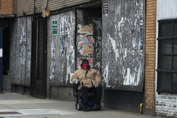 FILE - An unidentified African American man navigates his wheelchair in Chicago's Hyde Park neighborhood, in Chicago, Illinois, April 6, 2020.