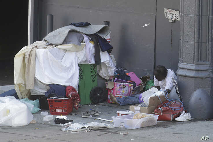 FILE - A homeless African American sits on a sidewalk amid the coronavirus pandemic, in San Francisco, California, April 2, 2020.