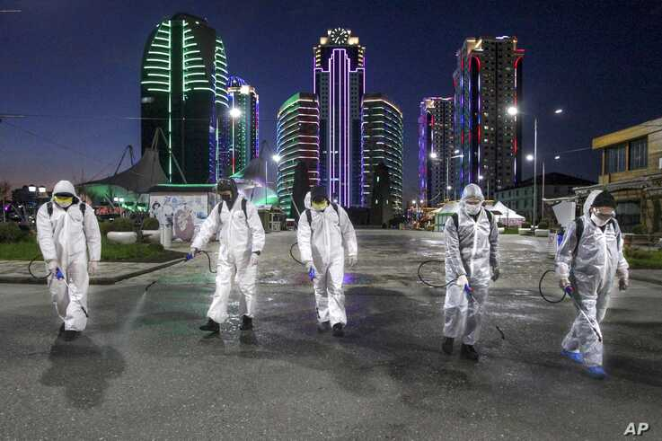 FILE - Municipal workers wearing protective suits spray disinfectant in an area in the center of Grozny, capital of Russia's Chechnya region, April 6, 2020. Ramzan Kadyrov, the region's strongman, has taken extreme measures to fight the spread of the new coronavirus in Chechnya.