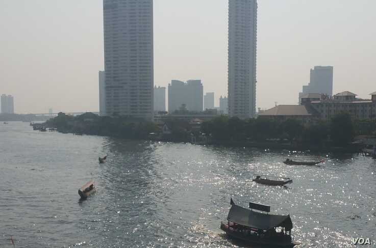 Boats float along the river in Bangkok, which is facing rising sea levels and sinking land. (VOA News)