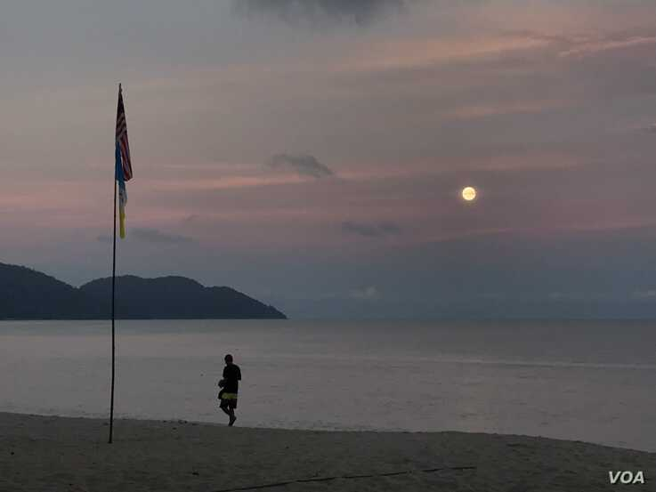 The sun sets on the beach in Penang, where one citizen jumped into the sea to avoid arrest for violating Malaysia's virus lockdown order.