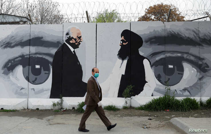 FILE - An Afghan man wearing a protective face mask walks past a mural depicting U.S. peace envoy for Afghanistan Zalmay Khalilzad, left, and Taliban chief negotiator Mullah Abdul Ghani Baradar, in Kabul, Afghanistan, April 13, 2020.