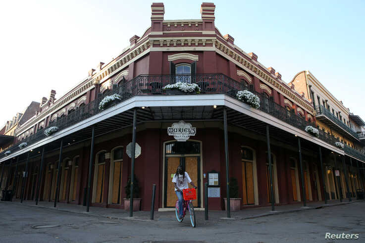 FILE - A man rides his bicycle in front of a boarded up French Quarter restaurant amid the outbreak of the coronavirus, in New Orleans, Louisiana, March 25, 2020.