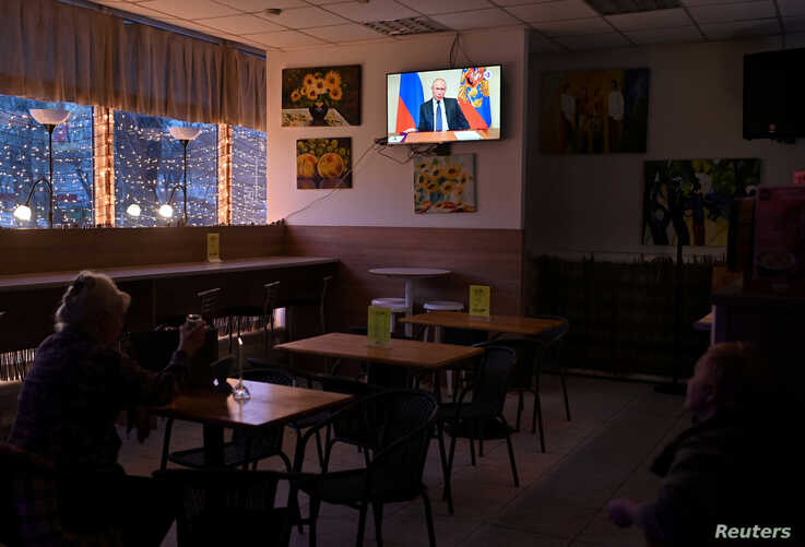 FILE - People watch a broadcast of Russian President Vladimir Putin's address to the nation on measures to combat the spread of the coronavirus, in a cafe in Omsk, Russia, March 25, 2020.