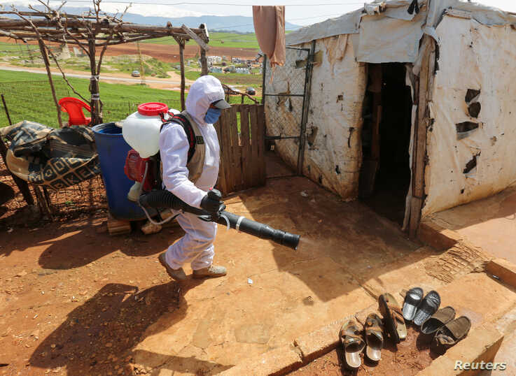 A worker from the municipality sanitizes Syrian refugee camp, as Lebanon extends a lockdown to combat the spread of coronavirus disease (COVID-19) in Marjayoun, Lebanon, March 23, 2020.