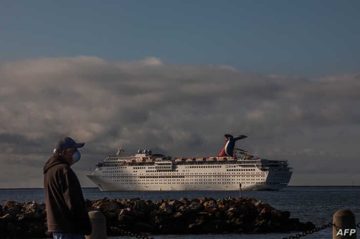 A man wearing a face mask as a preventive measure against the spread of the COVID-19 Coronavirus, looks at Cruise Ships docked…