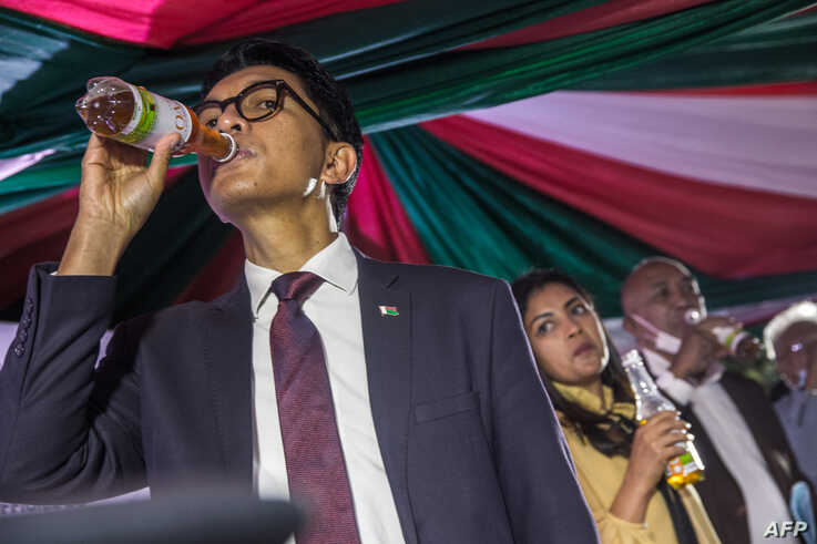 "Madagascar's President Andry Rajoelina drinks a sample of the ""Covid Organics"" or CVO remedy at a launch ceremony"