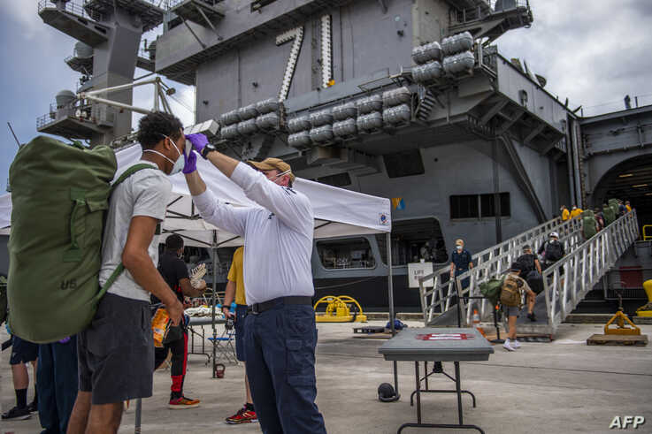 (FILES) In this file US Navy handout photo obtained May 3, 2020 Sailors assigned to the aircraft carrier USS Theodore Roosevelt…