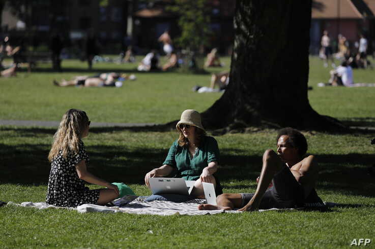 People enjoy the sunshine in London Fields, north east London on May 20, 2020, as temperatures in the capital are expected to…