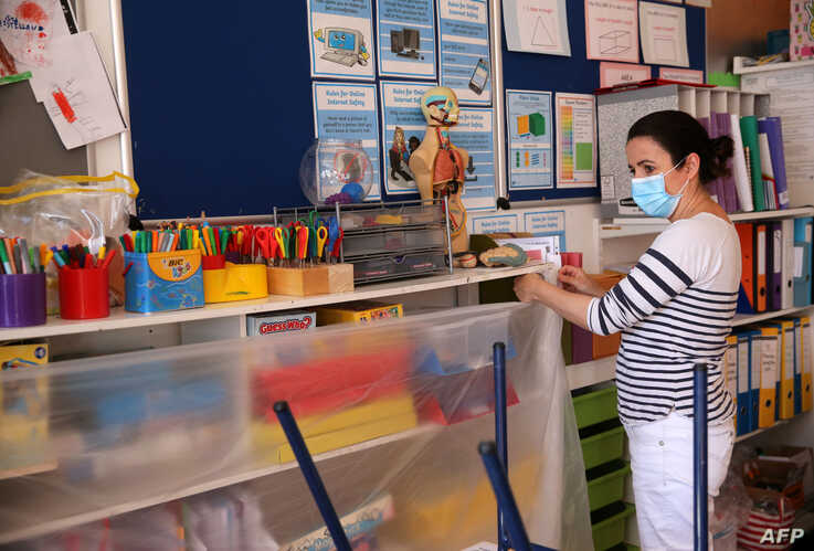 French coordinator Julie Bonaz covers a bookshelf with plastic to help provide a teaching environment safe from Coronavirus for…