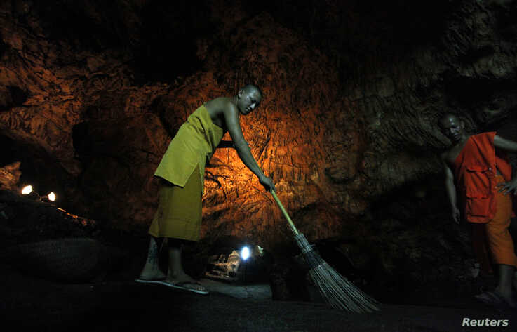 A Buddhist monk sweeps up bat guano in a cave near Wat Khao Cong Phran Temple in Ratchaburi province, 130 km (81 miles) west of…