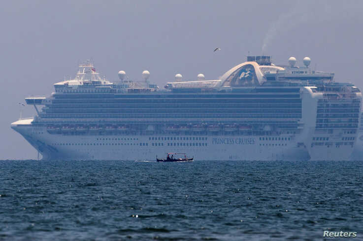 A fishing boat sails past the Princess Cruises' Ruby Princess cruise ship as it docks in Manila Bay during the spread of the…
