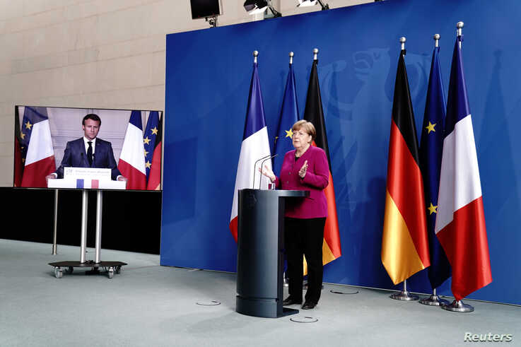 German Chancellor Angela Merkel holds a joint video news conference with French President Emmanuel Macron in Berlin, Germany,…