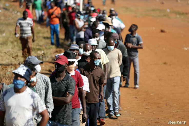 People wearing protective face masks stand in a queue to receive food aid amid the spread of the coronavirus disease (COVID-19…