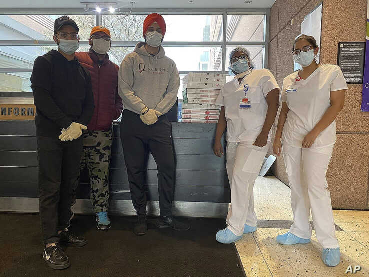 Japneet Singh, center, and two other volunteers deliver pizza to health care workers