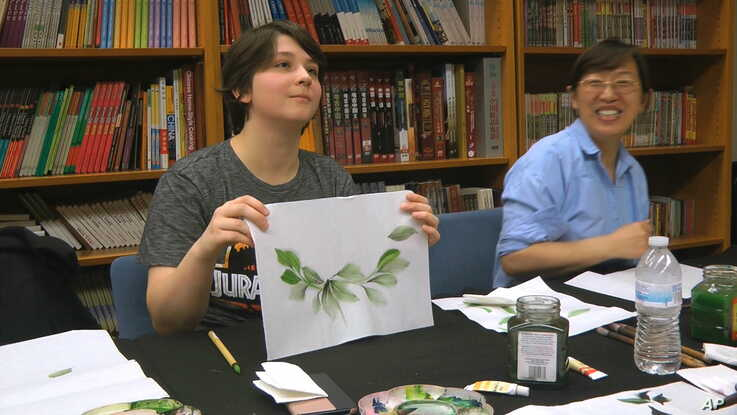 Undergraduate student Moe Lewis, left, shows her watercolor painting of peony leaves at a traditional Chinese painting class.