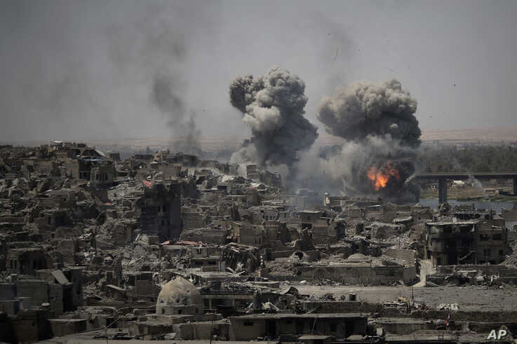 FILE - In this July 11, 2017, file, photo, airstrikes target Islamic State positions on the edge of the Old City a day after…