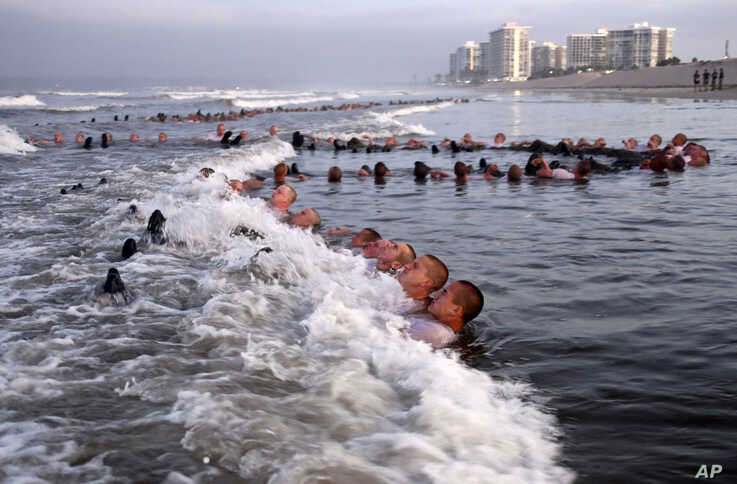 """This May 4, 2020, photo provided by the U.S. Navy shows SEAL candidates participating in """"surf immersion."""""""