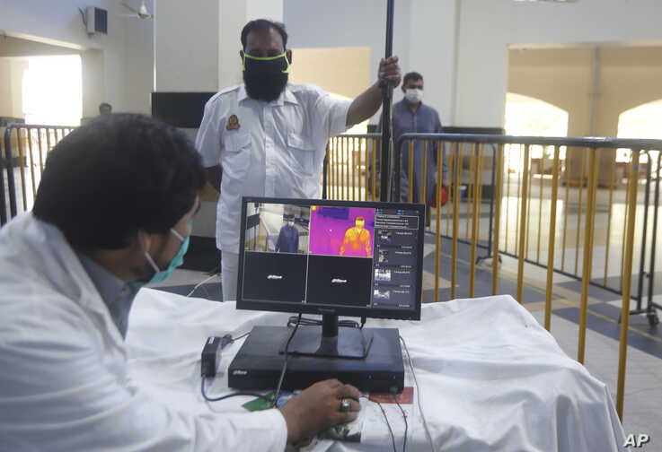 Pakistani railway staff use thermal scanner to check visitors for coronavirus symptoms at Lahore railway station in Pakistan, May 6, 2020.
