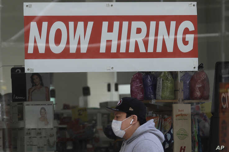 A man wears a mask during the coronavirus outbreak while walking under a Now Hiring sign at a CVS Pharmacy in San Francisco,…