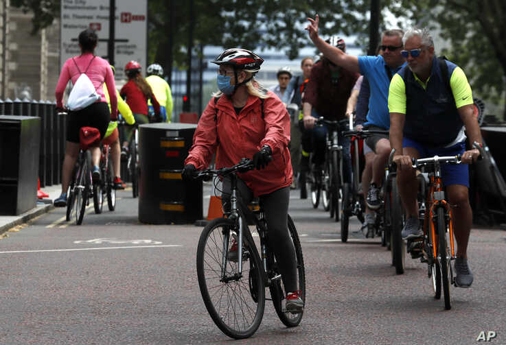 People cycle through Westminster area of London, Sunday, May 10, 2020 during the nation-wide coronavirus lockdown.