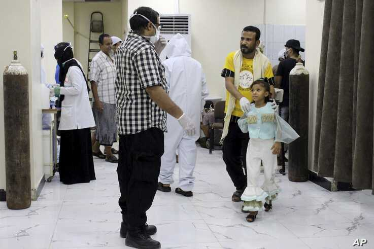 In this May 12, 2020 photo, Yemeni medical workers wearing masks and protective gear talk to patients at hospital in Aden,…