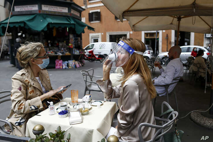 A woman sips her coffee from under her facial protection at a cafe with outdoor tables in Rome Monday, May 18, 2020. Italy is…