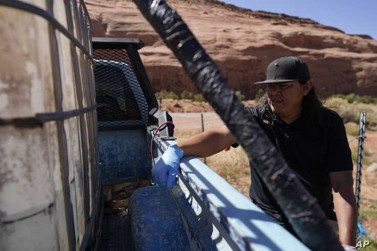 FILE - Chris Topher Chee waits for water to fill a tank in his truck in Oljato-Monument Valley, Utah, on the Navajo reservation, April 27, 2020. People living in rural or tribal communities are among the toughest to count in the U.S. census.
