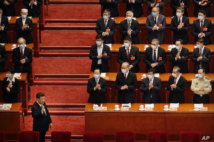 Chinese President Xi Jinping, left, gestures as he arrives for the opening session of the Chinese People's Political…