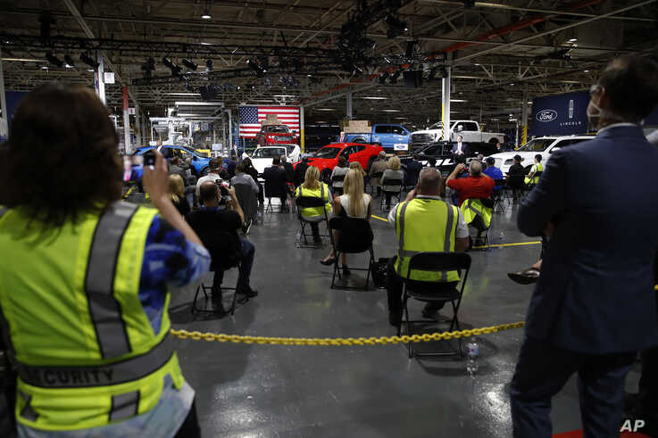 People listen as President Donald Trump speaks at Ford's Rawsonville Components Plant that has been converted to making…