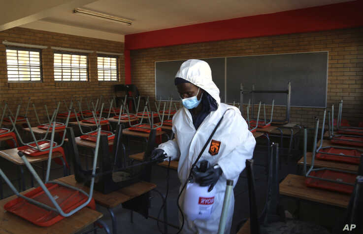 A worker from Bidvest Prestige wearing protective gear, sprays disinfectant in a classroom