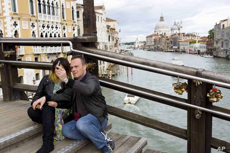 FILE - A couple takes its picture on the Ponte dell'Accademia (Academia bridge) spanning the Grand Canal in Venice, northern Italy.
