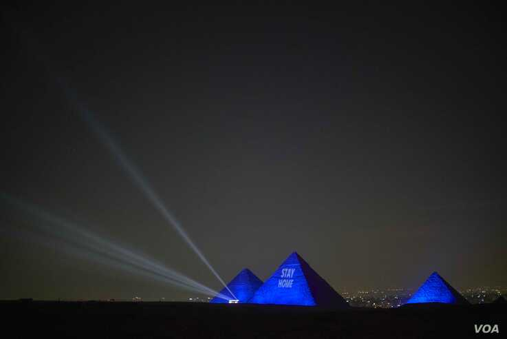 """The Great Pyramids of Giza are lit up with a message saying, """"Stay Home,"""" April 18, 2020. (Hamada Elrasam/VOA)"""